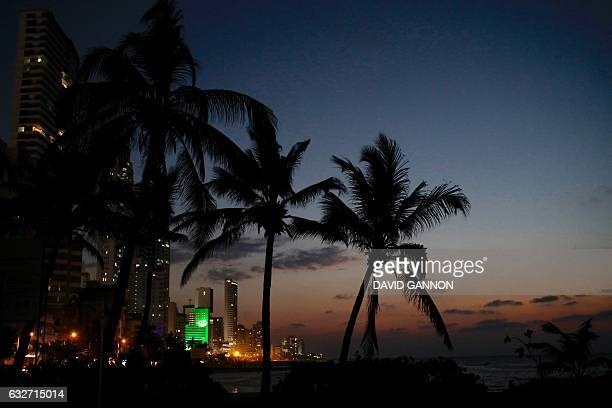 The sun sets behind the beachside skyline in the Bocagrande district in Cartagena Colombia on January 25 2017 / AFP / David GANNON