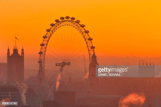 TOPSHOT The sun sets behind the Houses of Parliament and the London Eye in central London on December 28 2016 London's stock market hit December 28...