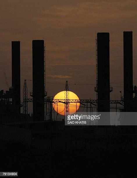 The sun sets behind the main Palestinian electricity company AlNuseirat in the central Gaza Strip 20 January 2008 Gaza reeled from power outages...