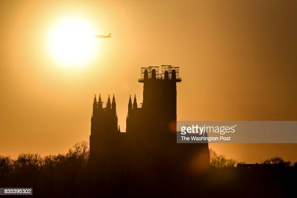 The sun sets behind the National Cathedral as a plane flies in direction to Ronald Reagan National Airport on an early spring afternoon in Washington...