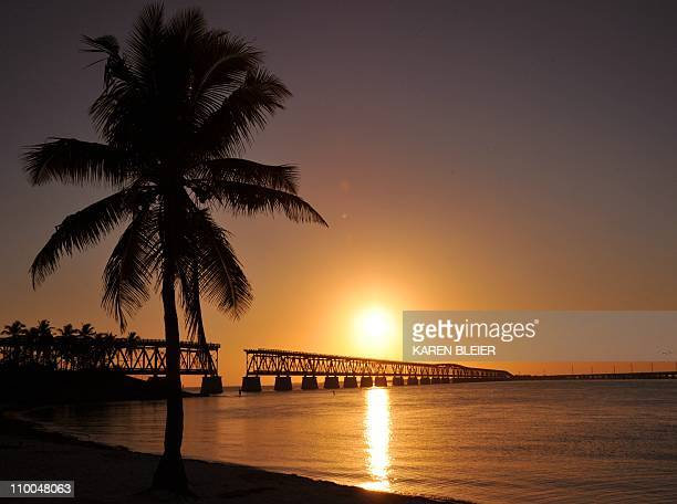 The sun sets behind the old railway bridge in the Bahia Honda State Park in Bahia Honda Key Florida February 25 2011 AFP PHOTO/Karen BLEIER
