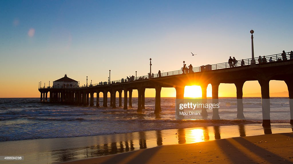 The sun sets behind the pier after the second day of competition at the 55th AVP Manhattan Beach Open on August 16 2014 at Manhattan Beach Pier in...