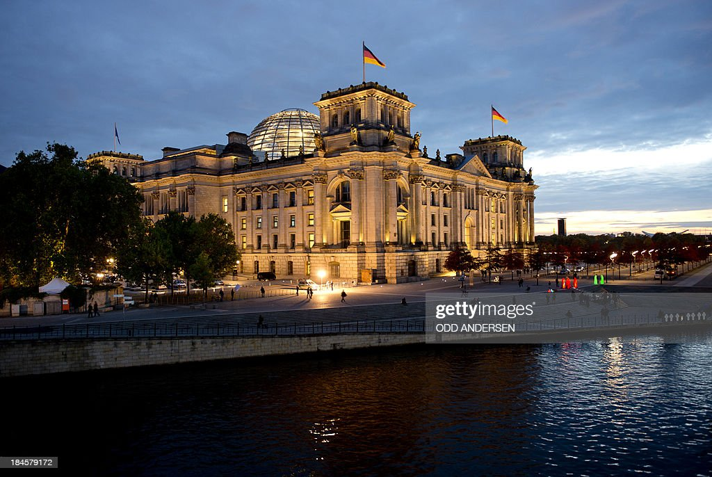 The sun sets behind the Reichstag (R), the building housing the German lower house of parliament during the 2nd round of exploratory talks on forming a coalition government in Berlin on October 14, 2013. The exploratory talks with the left-leaning ecologist party are part of Merkel's hunt for a governing partner after her conservatives won September 22 elections but fell short of a ruling majority.
