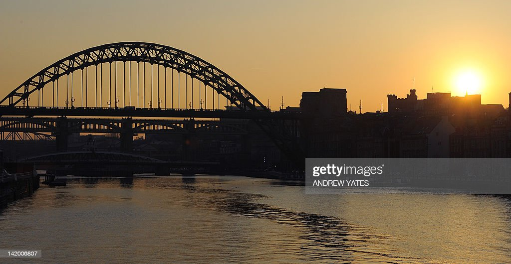 The sun sets behind the Tyne Bridge over the River Tyne shot from the Gateshead Millennium Bridge in Newcastle, north-east England, on March 27, 2012.