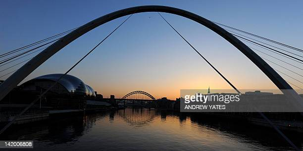 The sun sets behind the Tyne Bridge over the River Tyne shot from the Gateshead Millennium Bridge in Newcastle northeast England on March 27 2012 AFP...