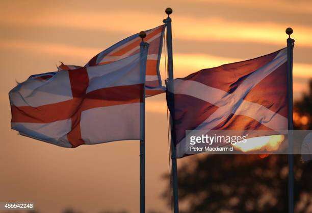 The sun sets behind the Union flag the flag of England and the Scottish Saltire on September 16 2014 in Gretna Green Scotland Yes and No supporters...