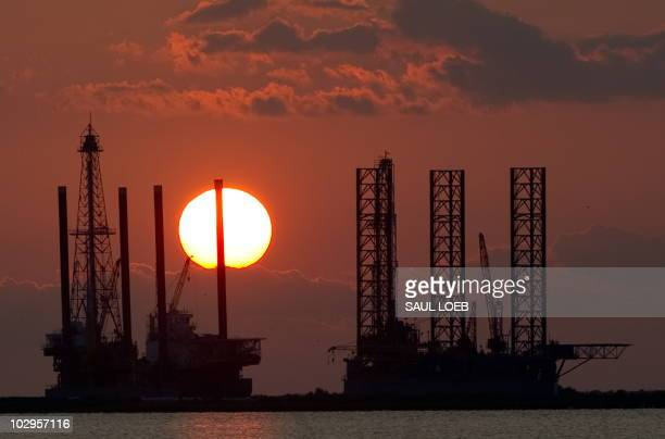 The sun sets behind two under construction offshore oil platform rigs in Port Fourchon Louisiana June 14 as cleanup continues on the BP Deepwater...