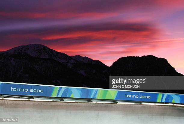 The sun sets in a blaze of color over the mountains above the luge track during a training session 07 February 2006 in Cesana Pairol at the 2006...