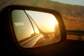 The sun sets in a car wing mirror on a road trip.\
