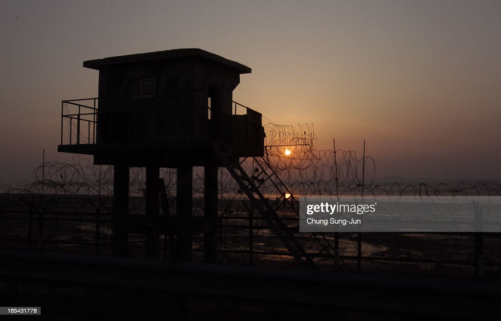 The sun sets near a barbed-wire checkpoint near the border village of Panmunjom on April 4, 2013 in Paju, South Korea. Still 400 South Korean remain in the joint industrial park fearing they can not get back there once return to South. In recent weeks North Korea have threatened to attack South Korea and U.S. military bases, with South Korean and American intelligence identifying what is believed to be an intermediate-range missile being moved by North Korea to its eastern coast, in preparation for a planned strike.
