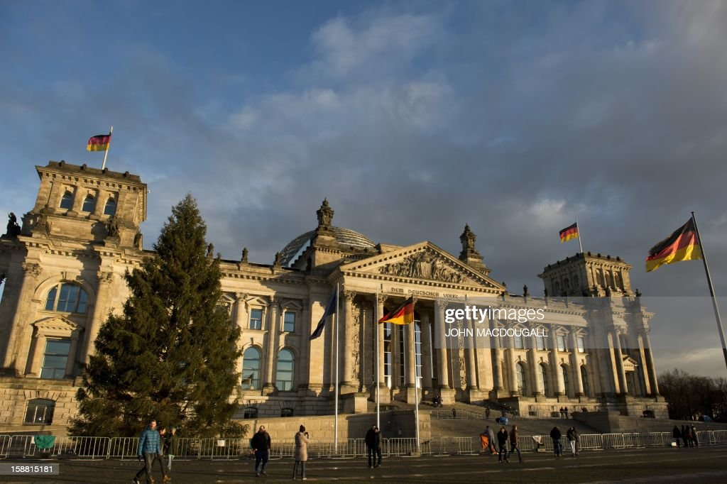 The sun sets on Berlin's Reichstag building which houses Germany's lower house of parliament, December 30, 2012. AFP PHOTO / JOHN MACDOUGALL