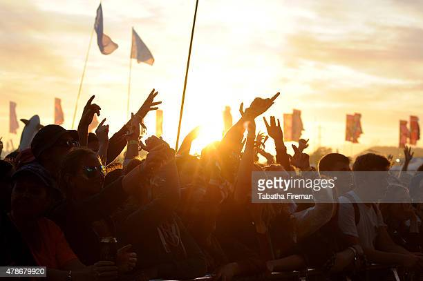 The sun sets on the festival crowd at the Glastonbury Festival at Worthy Farm Pilton on June 26 2015 in Glastonbury England
