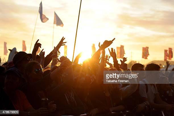The sun sets on the festival crowd at the Glastonbury Festival at Worthy Farm Pilton on June 26 2015 in Glastonbury England