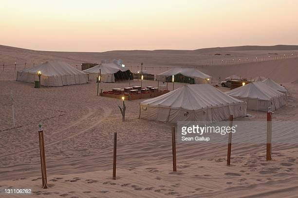 The sun sets over a desert camp of tents for tourists on October 30 2011 near Umm Sa'id Qatar Camel safaris and fourwheel drive tours of the desert...