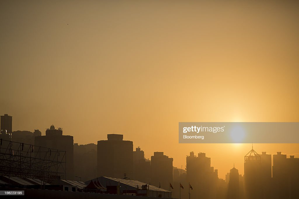 The sun sets over buildings in Hong Kong Island's Western District, viewed from Harbour City shopping mall, operated by Wharf (Holdings) Ltd., in the Tsim Sha Tsui district of Hong Kong, China, on Friday, Nov. 9, 2012. Wharf (Holdings) Ltd. is controlled by the family of billionaire Chairman Peter Woo. Photographer: Jerome Favre/Bloomberg via Getty Images