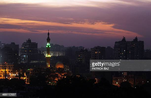 The sun sets over Cairo as the mosque of alAguza neighbourhood appears in the foreground on November 28 2010 AFP PHOTO/PATRICK BAZ