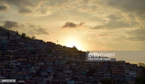 TOPSHOT The sun sets over crowded housing in Jalousie neighborhood of Petion Ville commune in the Haitian capital PortauPrince on June 12 2017 / AFP...
