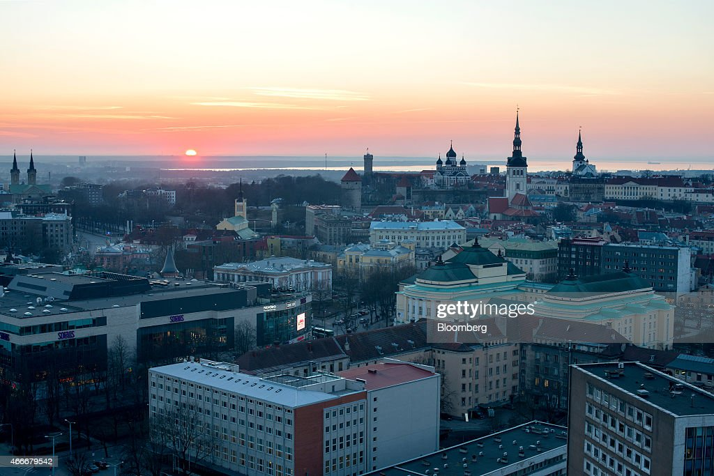 The sun sets over the Baltic Sea beyond historical buildings standing in the Old Town top on the city skyline in Tallinn Estonia on Tuesday March 17...