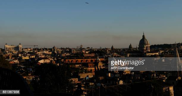 The sun sets over the city of Rome on August 14 2017 / AFP PHOTO / Alberto PIZZOLI