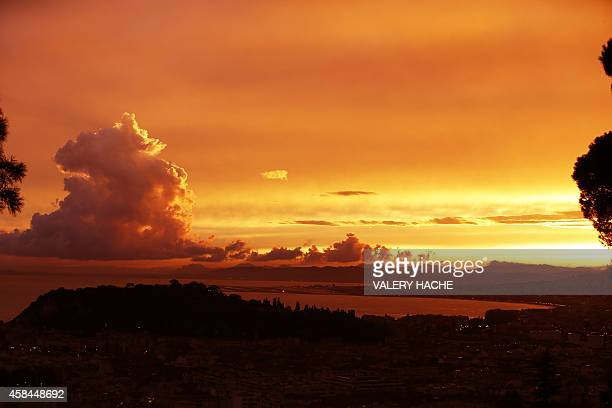 The sun sets over the French Riviera city of Nice southeastern France on November 5 the day after heavy storms battered the Mediterranean coastline...