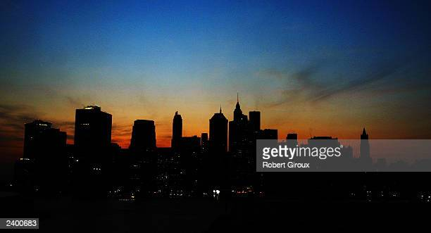 The sun sets over the Manhattan skyline August 14 2003 during a major power outage affecting a large part of the north eastern United States and...