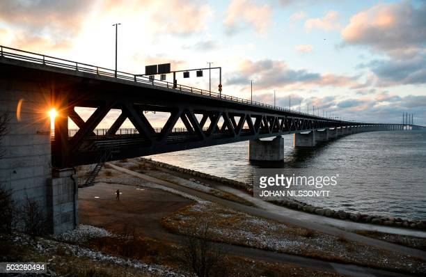 The sun sets over the Oresund Bridge between Sweden and Denmark in Malmo Sweden on January 3 2016 Swedish authorities on January 4 will introduce...