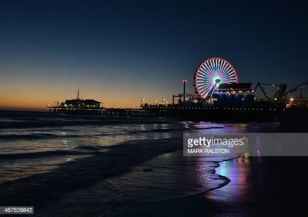 The sun sets over the Pacific Amusement Park at Santa Monica pier California on October 19 2014 The pier which will soon celebrate its 100th year of...