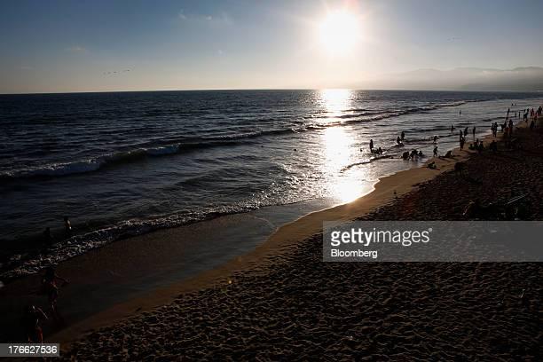 The sun sets over the Pacific Ocean as beach goers swim in the ocean near the Santa Monica Pier in Santa Monica California US on Monday Aug 5 2013...