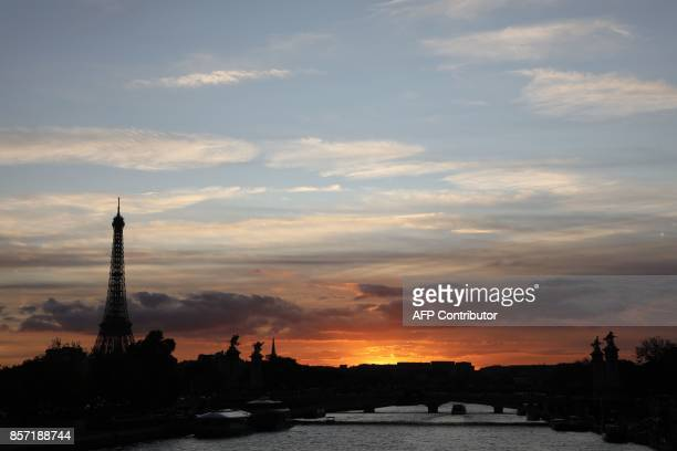 The sun sets over the River Seine near the Eiffel Tower in Paris on October 3 2017 / AFP PHOTO / LUDOVIC MARIN