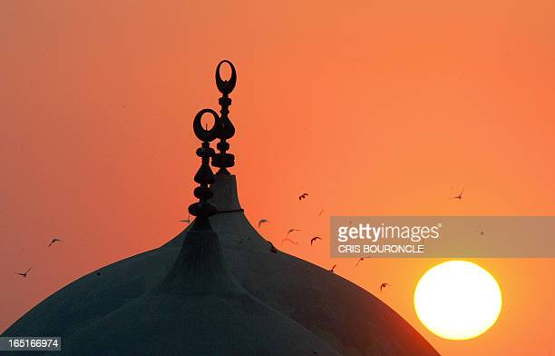 The sun sets over the twin domes of the Fatma AlNabawiyya Mosque in the old Muslim district of Darb AlAhmar in Cairo 23 March 2005 AFP PHOTO/CRIS...
