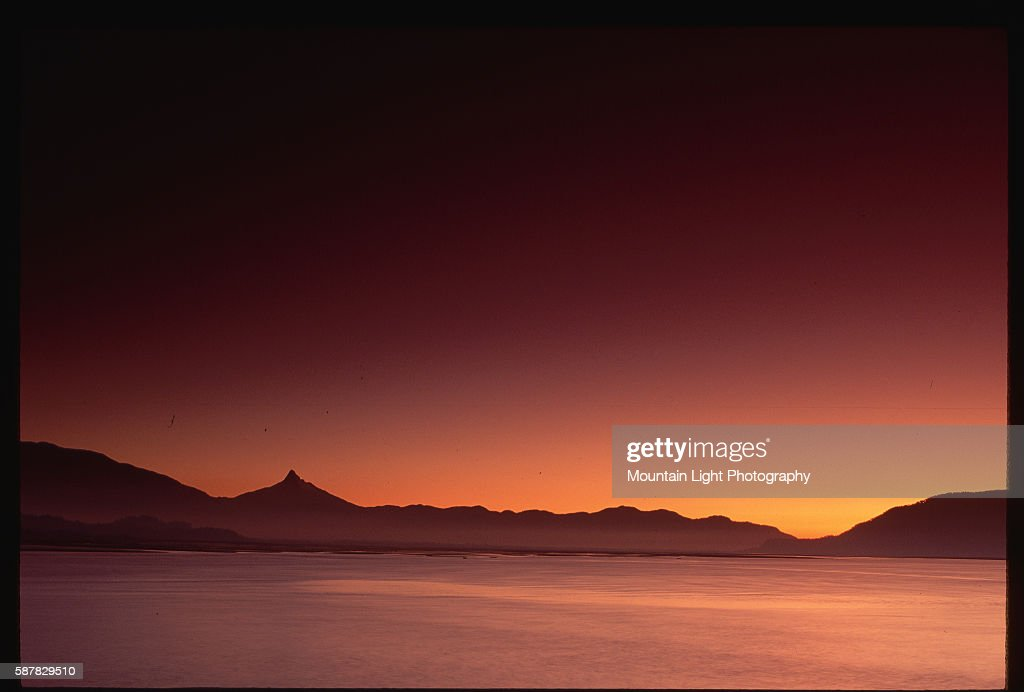 The sun sets over Volcan Corcovado and a lake Chilean Patagonia Chile   Location Los Lagos Region Chile