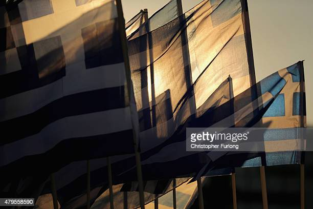 The sun sets through Grrek flags over the Greek parliament as the polls have now closed in the Greek austerity referendum and people are begining to...