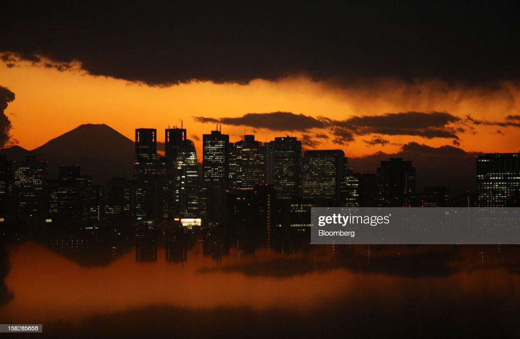 The sun setting behind buildings in front of Mount Fuji is reflected on a table in Tokyo, Japan, on Wednesday, Dec. 12, 2012. Japan's economy shrank in the last two quarters, meeting the textbook definition of a recession, as the dispute with China, the country's biggest export market, caused consumers there to shun Japanese products and contributed to Japan's worst year for exports since the global recession in 2009. Photographer: Tomohiro Ohsumi/Bloomberg via Getty Images