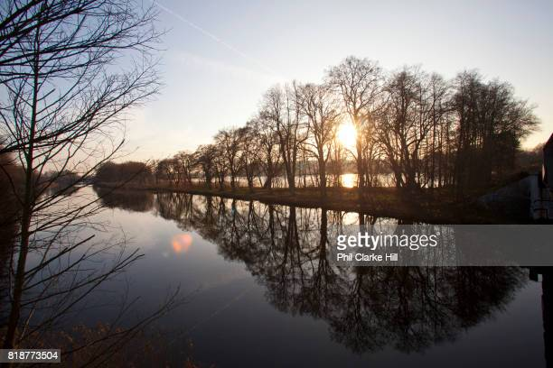 The sun setting over a lake in Uckermarkische Seen Natural park part of the The Feldberg Lake District Nature Park containing large lakes kettle bogs...