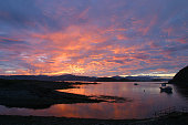 The sun setting over the inner Hebridean island of Mull as seen from the neighbouring island of Easdale on Scotland's rugged and mountainous west...