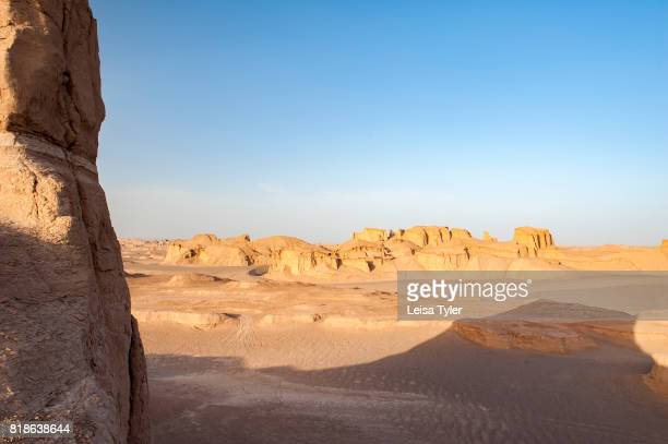 The sun setting over yardangs in the Lut Desert in Shahad Iran Known as kaluts in Iran yardangs are geological formations that have been created by...