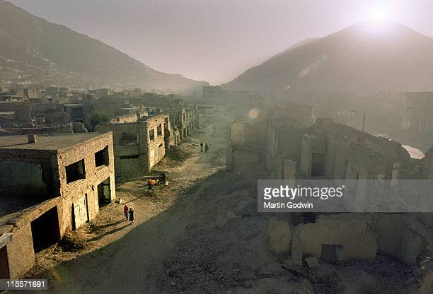The sun settnig over ruined buildings in an Afghan town with a central dirt street with rubble and mountains in the distance near Kabul a year after...
