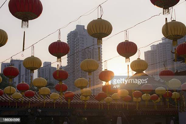 The sun shines behind lanterns at the Wong Tai Sin temple in Hong Kong on October 28 2013 The Taoist temple is a major tourist attraction and centre...