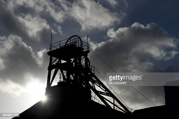 The sun shines behind the headframe of a shaft mine at the National Coal Mining Museum based on the site of the former Caphouse Colliery in Overton...