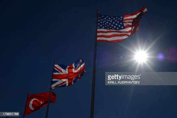 The sun shines behind Turkish British and US flags at the G20 summit on September 6 2013 in Saint Petersburg World leaders at the G20 summit on...