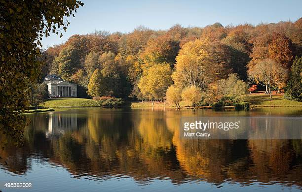 The sun shines on trees displaying their autumn colours surrounding the lake at the National Trust's Stourhead on November 2 2015 in Wiltshire...