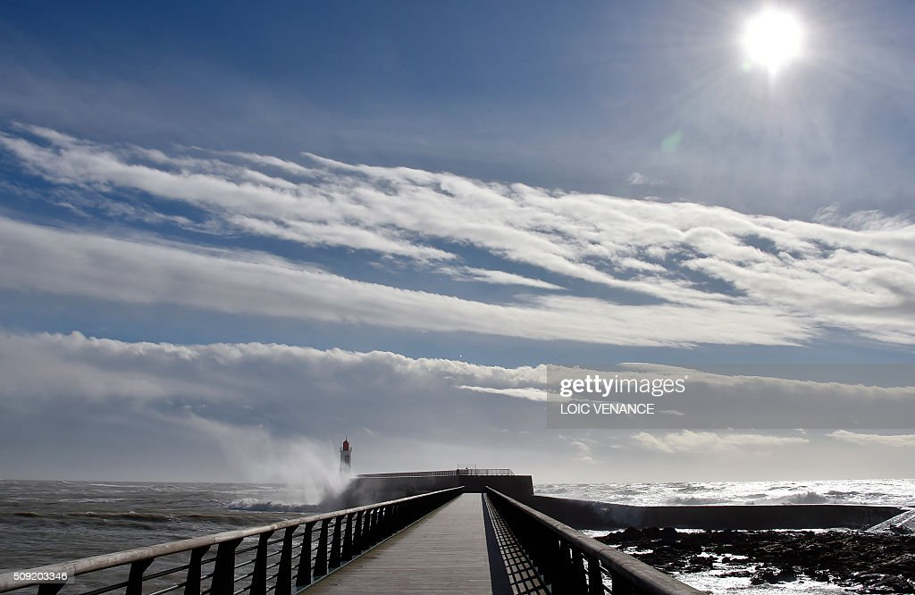 The sun shines over a pier in Les Sables-d'Olonne, western France, on February 9, 2016. High winds buffeted northwestern Europe on February 8, leaving one woman in France in a coma after she was hit by an advertising hoarding. Electricity was cut to 5,000 homes in northern France. / AFP / LOIC VENANCE