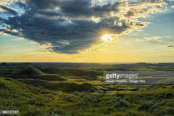 The sun shines through a cloud over the Killdeer Badlands, Grasslands National Park