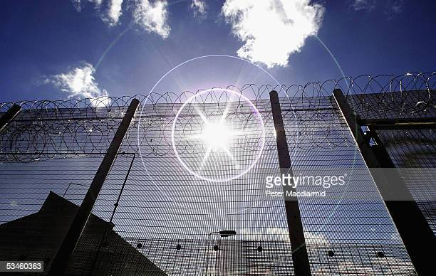 The sun shines through high security fencing surrounding Norwich Prison on August 25 2005 in Norwich England A Chief Inspector of Prisons report on...