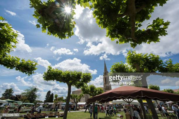 the sun shining through the lime trees at a local fair on June 5 2017 in Saussignac France Monday is a public holiday in France to celbrate the day...