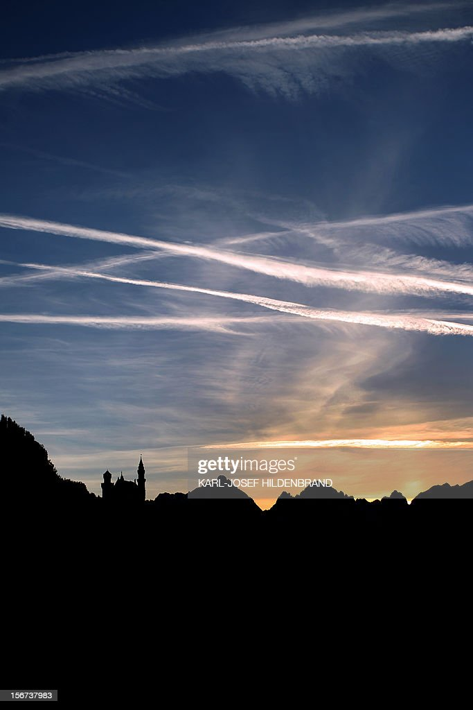 The sun stes behind the Neuschwanstein Castle and the Alps near Hohenschwangau, western Germany, on November 19, 2012. AFP Photo / KARL