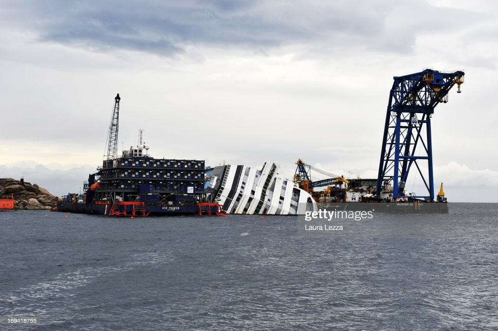 The sunken Costa Concordia remains in the water during a commemoration for the victims on January 13, 2013 in Giglio Porto, Italy. A year after the sinking of the ship Costa Concordia, relatives of the victims, survivors, island residents, law enforcement and institutions gathered to mark the first anniversary and commemorate the dead. More than four thousand people were on board when the ship hit a rock off the Tuscan coast, killing 32 and leaving two people missing.