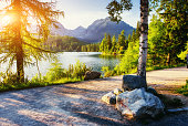 The sunrise over a lake in the park High Tatras. Shtrbske Pleso, Slovakia, Europe.