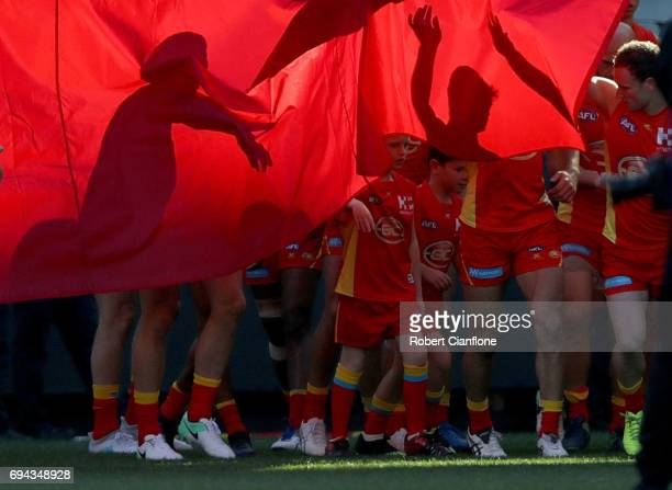 The Suns break through the banner during the round 12 AFL match between the Hawthorn Hawks and the Gold Coast Suns at Melbourne Cricket Ground on...