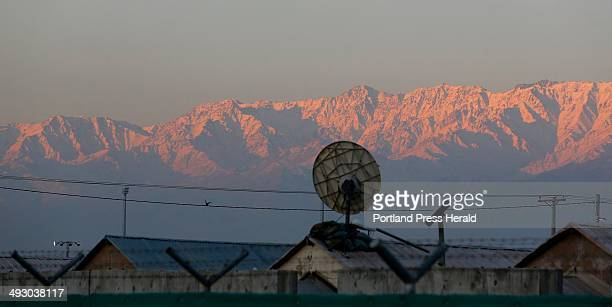 The sun's early rays hit the snowcapped mountains that surround Bagram Airfield in Afghanistan Friday December 20 as the BHuts in the foreground...